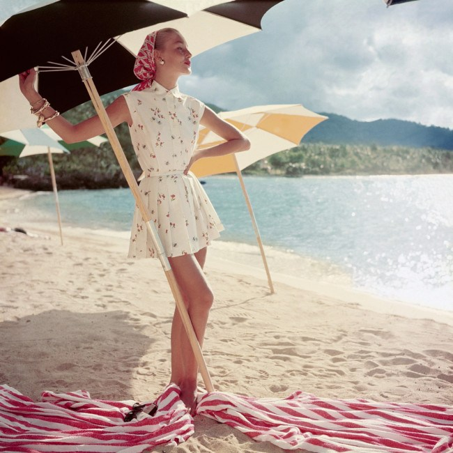model-standing-under-beach-umbrella-wearing-a-summer-dress-1954